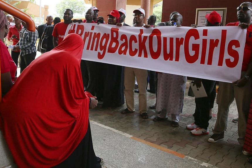 Members of the #BringBackOurGirls campaign group wait along a corridor of the Federal High Court, to challenge the Nigerian police's ban on their daily protests, in Mataima, Abuja on June 3, 2014. Supporters of the more than 200 schoolgirls abdu