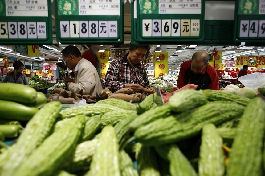 Customers shop at a supermarket in Beijing, on April 16, 2014. -- PHOTO: REUTERS