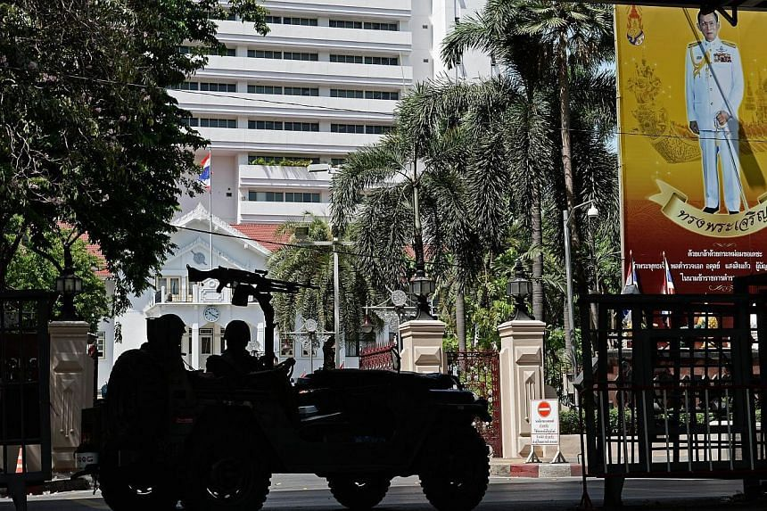 """Thai army soldiers secure an area in front of the Royal Thai Police headquarters, adorned with a portrait of King Bhumibol Adulyadej (right). Thailand's military is bolstering its self-designated role as protector of the monarchy by stepping up """""""