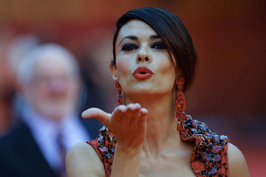 Italian actress Maria Grazia Cucinotta blows a kiss to fans at the red carpet of Shanghai International Film Festival opening ceremony in Shanghai on June 14, 2014.Shanghai last night kicked off its annual film festival, a nine-day event with a