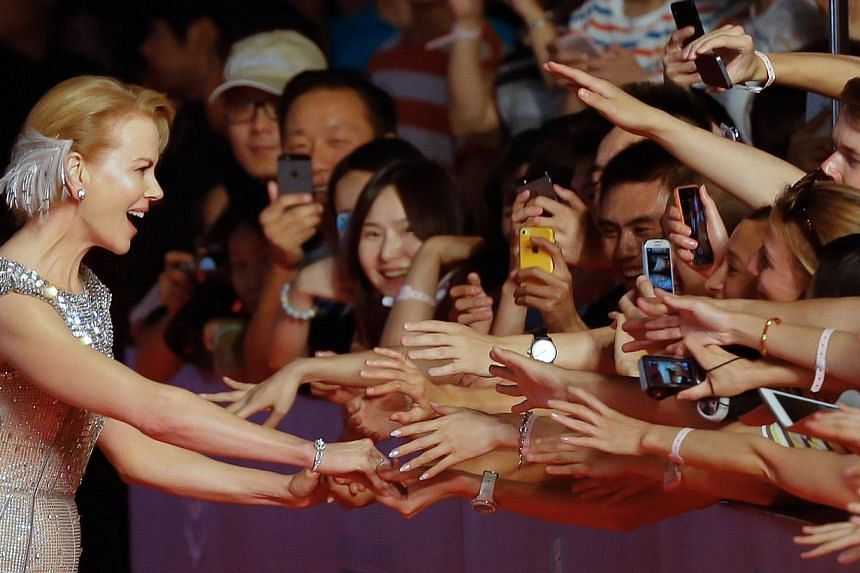 Australian actress Nicole Kidman (left) interacts with fans as she arrives at the red carpet of the Shanghai International Film Festival opening ceremony in Shanghai on June 14, 2014. Shanghai last night kicked off its annual film festival, a ni