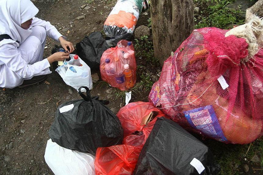 In this photograph taken on April 26, 2014, an Indonesian nurse at Klinik Bumi Ayu in Malang in the main island of Java, collects packs of recyclable garbage delivered by members of the clinic. Registered members of the unique clinic are mostly Indon