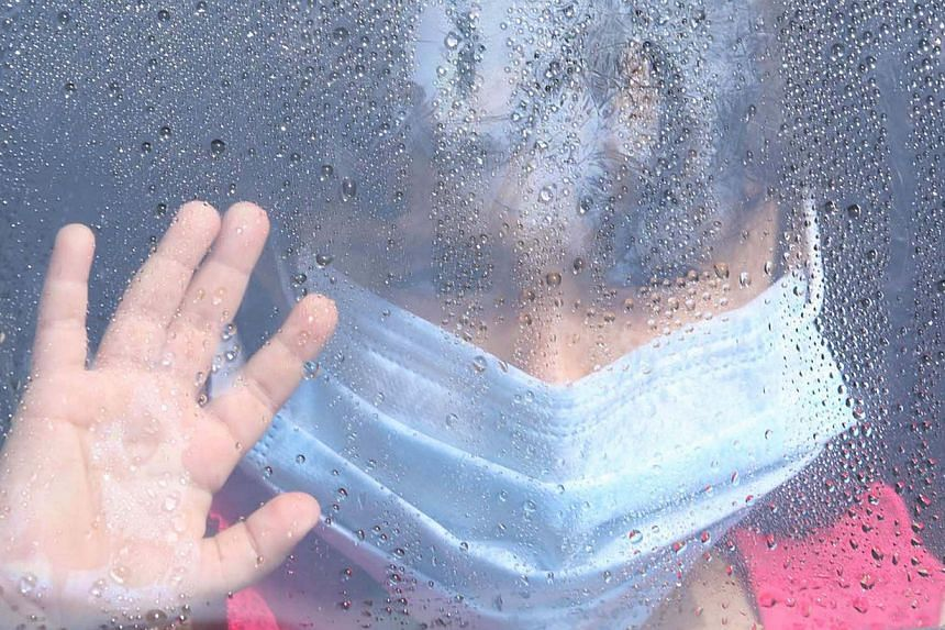 A girl wearing a mask looks out a car window as rain drops are seen in Taif, Saudi Arabia, on June 7, 2014. Saudi Arabia announced last week that it had found 113 more cases of the deadly Middle East Respiratory Syndrome (Mers). -- FILE PHOTO: REUTER