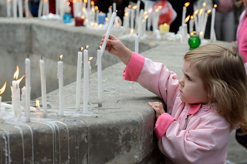 A girl places a candle during a memorial ceremony for the people killed when a Ukrainian military plane was shot by pro-Russian armed separatist militants on June 14, 2014, in the western Ukrainian city of Lviv. -- PHOTO: AFP