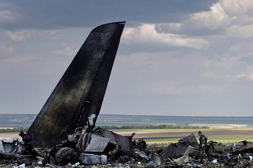 Pro-Russian separatists look through the debris of an IL-76 transporter which was taken down by pro-Russian rebels early on June 14, on the outskirts of Lugansk on June 14, 2014.Ukraine's president promised a tough response on Saturday to pro