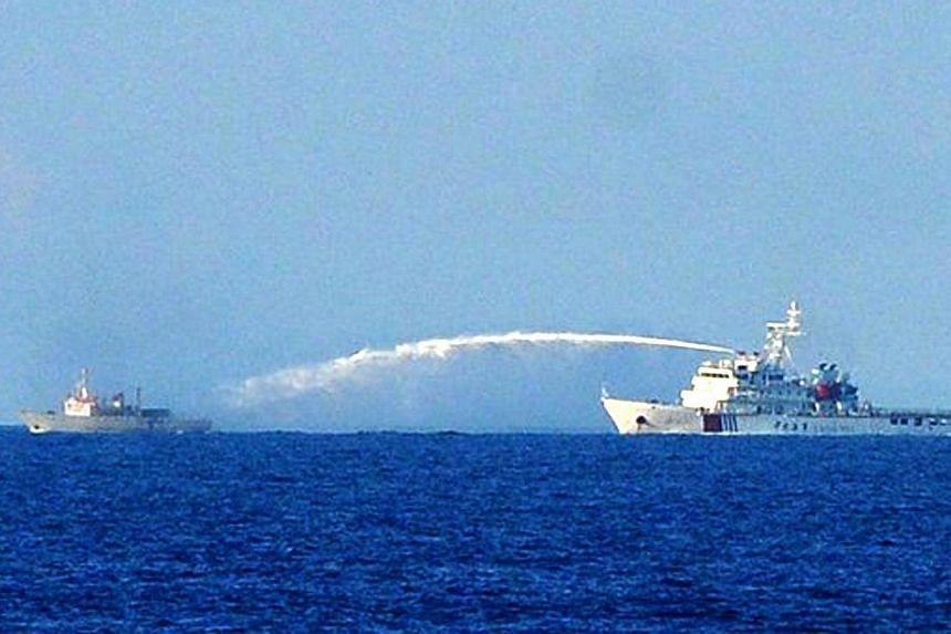 This picture taken on June 2, 2014 shows a Chinese Coast Guard ship (right) using a water cannon to attack a Vietnamese Fisheries Surveillance boat near to the site of the Chinese oil rig in disputed waters of the South China Sea off Vietnam's centra