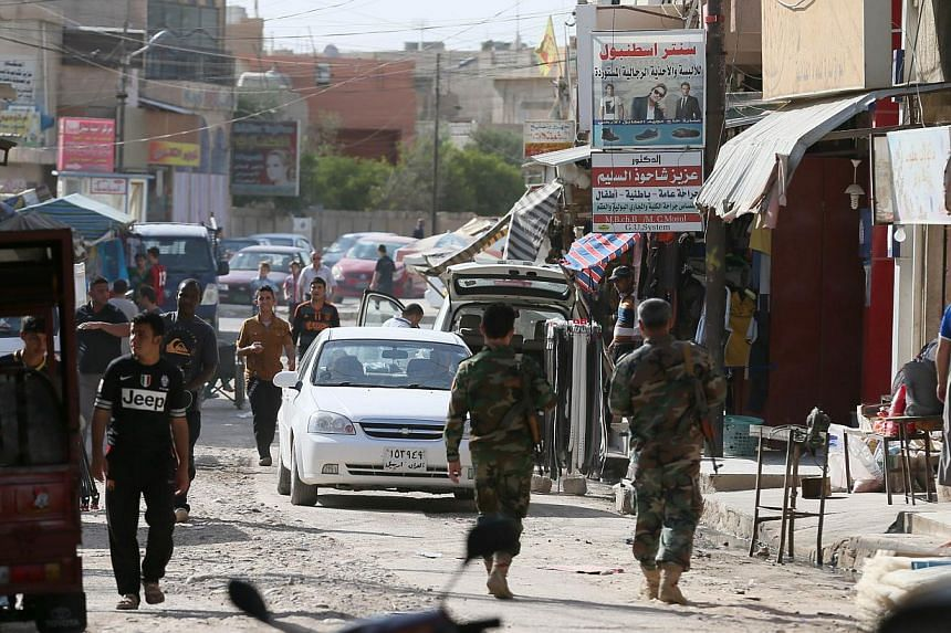 Iraqis walks along a street in the town of Bartala, on June 15, 2012, east of the northern city of Mosul, as some Iraqi police and security remain in the town to protect the local churches and community. The Obama administration is mulling possible d