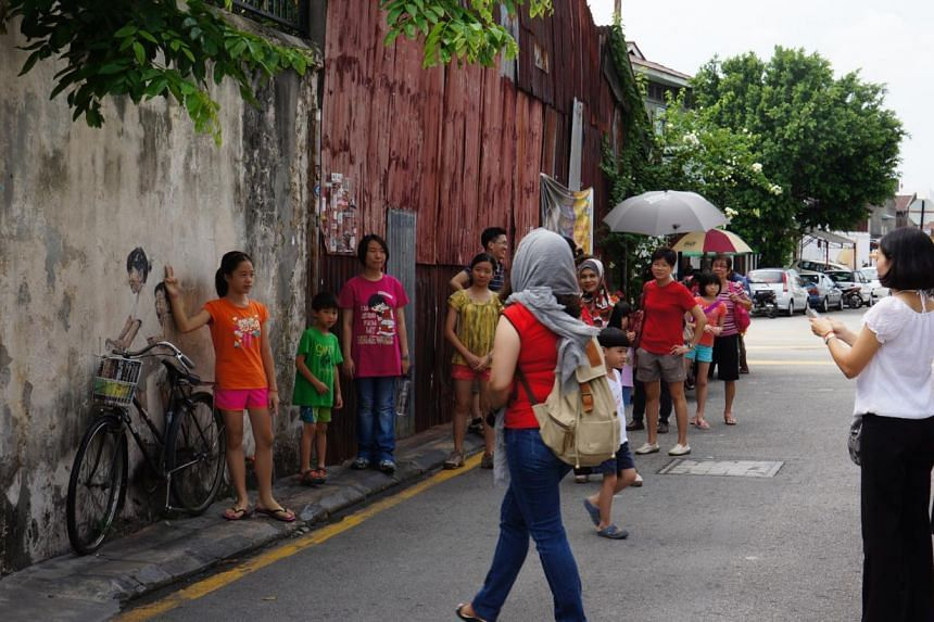 Daily queues to take photos of the most famous of George Town's murals. -- PHOTO: CAROLYN HONG