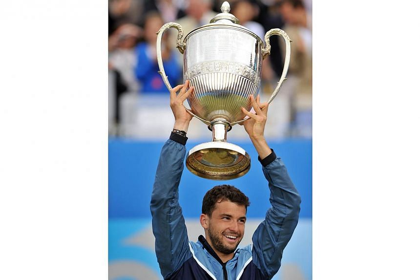 Bulgaria's Grigor Dimitrov celebrates with the trophy after victory over Spain's Feliciano Lopez in the final of the ATP Aegon Championships tennis tournament at The Queen's Club in west London, on June 15, 2014.  -- PHOTO: AFP