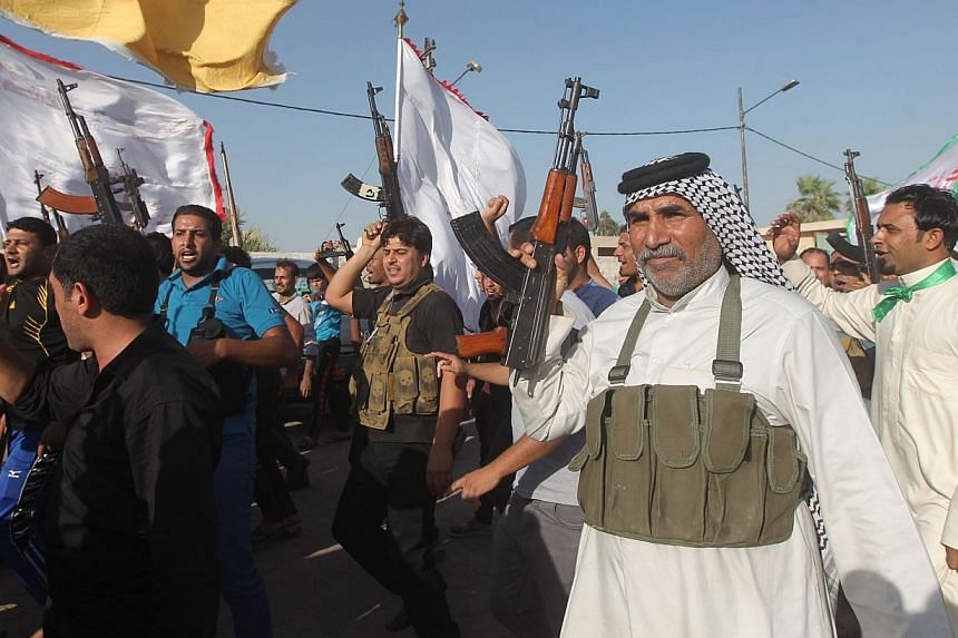Iraqi tribes men carry their weapons as they gather, volunteering to fight along side the Iraqi security forces against Jihadist militants who have taken over several northern Iraqi cities, in the capital Baghdad, on June 15 2014. -- PHOTO: AFP