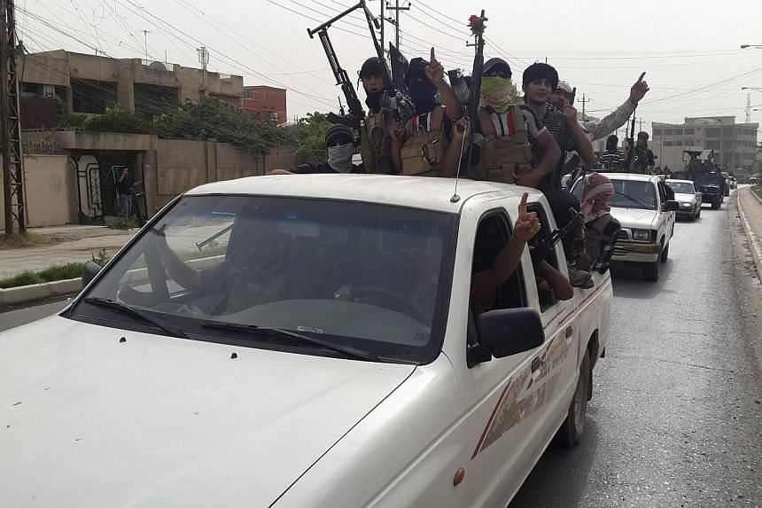 Fighters of the Islamic State of Iraq and the Levant (ISIL) celebrate on vehicles taken from Iraqi security forces, at a street in city of Mosul, on June 12, 2014. -- PHOTO: REUTERS