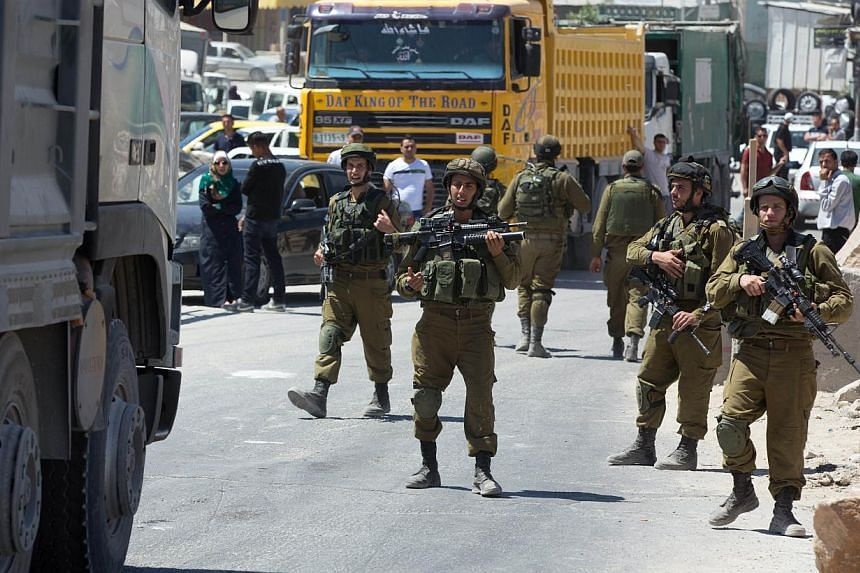 Israeli soldiers man a checkpoint in the West Bank town of Hebron on June 15, 2014. -- PHOTO: AFP