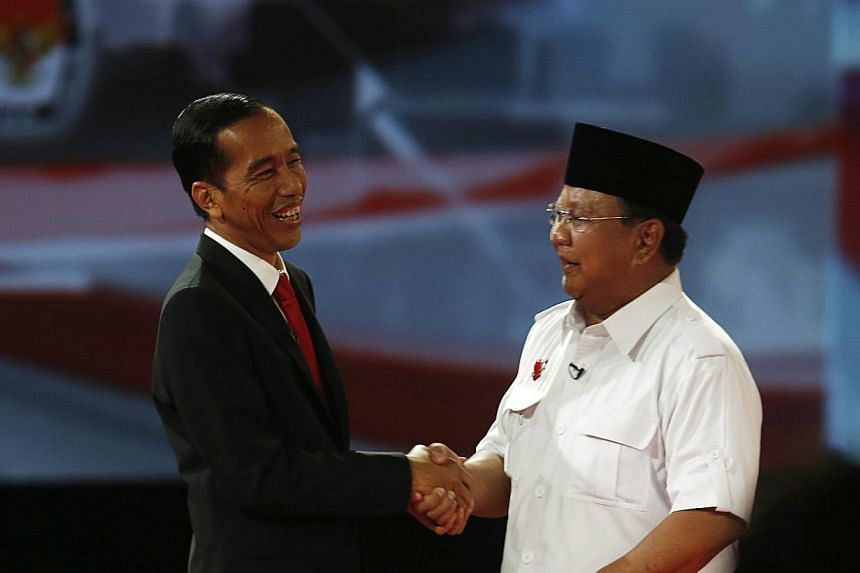 Indonesian presidential candidate Joko Widodo (left) shaking hands with his opponent Prabowo Subianto after a debate in Jakarta on June 15, 2014. Indonesia's two presidential candidates traded nationalist rhetoric on Sunday in a debate ahead of July'