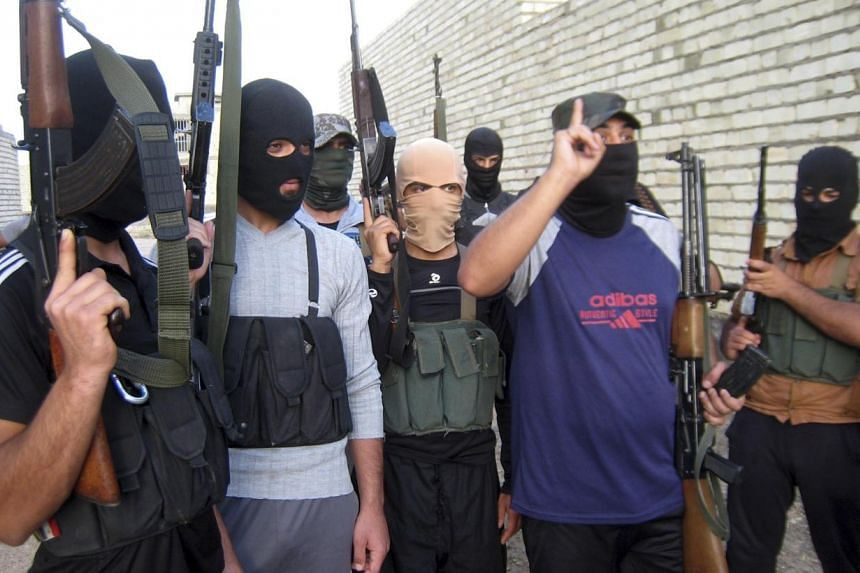 Masked Sunni gunmen pose for a photo during a patrol outside the city of Falluja on April 28, 2014. The New Straits Times newspaper reported on June 16, 2014 that at least 30 Malaysians have joined a militant group to fight in Iraq and Syria, an