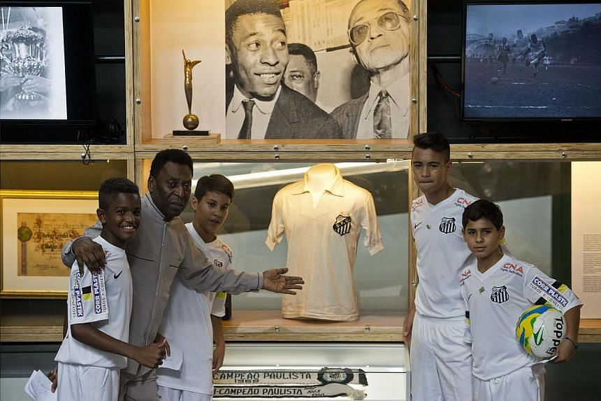 Brazilian football legend Edson Arantes do Nascimento (second from left), known as Pele, poses with young players during the inauguration of the Pele Museum, in Santos, some 70 km from Sao Paulo, Brazil, on June 15, 2014. -- PHOTO: AFP