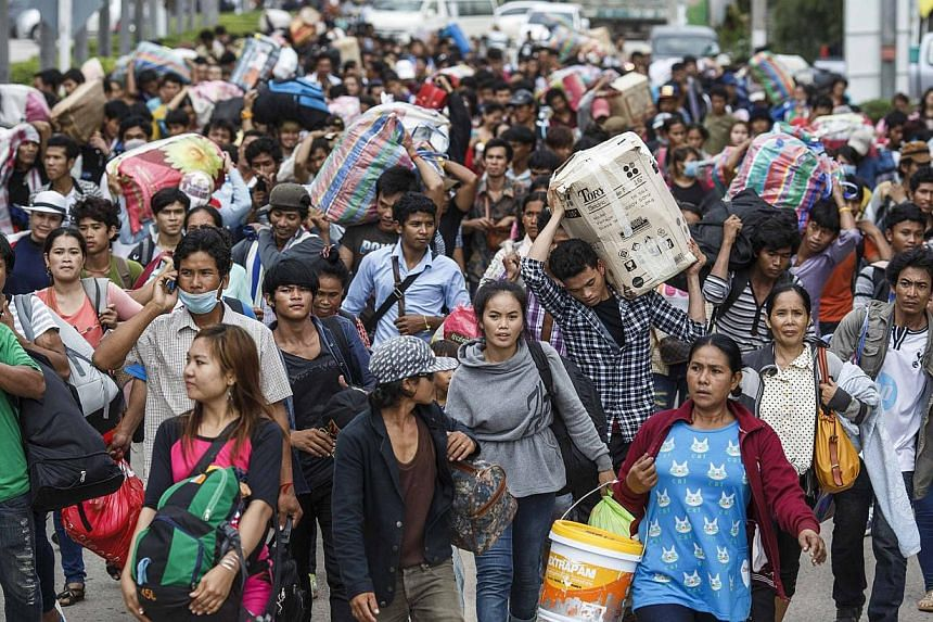 Cambodian migrant workers carry their belongings as they walk to cross the border at Aranyaprathet in Sa Kaew June 15, 2014. The International Organization for Migration (IOM) estimates that over the past week 100,000 Cambodians have poured over the