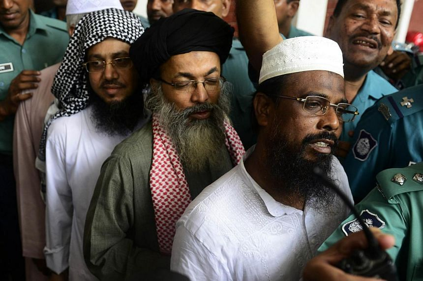 Harkat-ul Jihad al Islami (HUJI) leader Mufti Abdul Hannan (right) is flanked by police officers as he appears in court in Dhaka on June 16, 2014.A Bangladesh court on Monday delayed its verdict against a group of Islamic militants accused of c