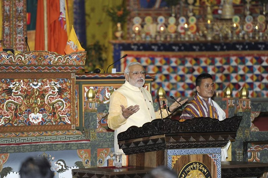 India's Prime Minister Narendra Modi (centre) addresses the joint session of the Parliament at Thimphu in Bhutan on June 16, 2014. India's Narendra Modi on Monday pledged stronger energy ties with tiny neighbour Bhutan as he wrapped up his first
