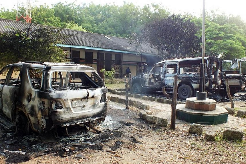 Charred vehicles sit outside a police station in Mpeketoni, in Lamu county along the Kenyan coast, after some 50 heavily-armed gunmen attacked the town near the coastal island and popular tourist resort of lamu the night before.Somalia's Al-Qae