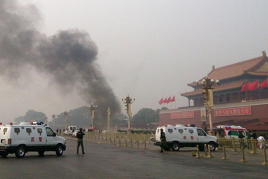 This file photo taken on Oct 28, 2013 shows police cars blocking off the roads leading into Tiananmen Square as smoke rises into the air after a vehicle loaded with petrol crashed in front of Tiananmen Gate in Beijing in an attack which left two peop