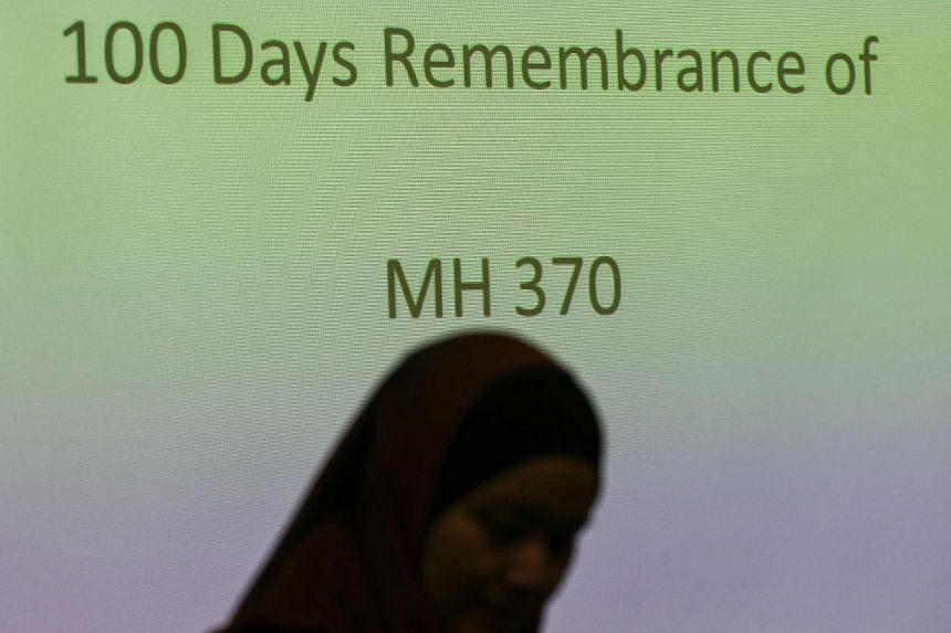 A family member of a Malaysian passenger on board the missing Malaysia Airlines Flight 370 stands near the during 100 Days Remembrance of MH370 in Kuala Lumpur June 15, 2014. -- PHOTO: REUTERS
