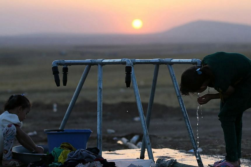 Iraqi children wash clothes and drink water at a temporary camp set up to house civilians fleeing violence, in Iraq's northern Nineveh province. Shiite Iran will consider working with longtime foe the United States if it takes the lead in helping pus