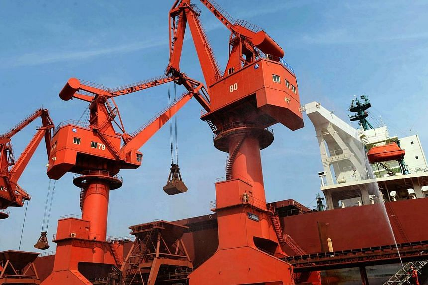 Iron ore being unloaded on a port in Qingdao, east China's Shandong province, in May 2014. -- PHOTO: AFP