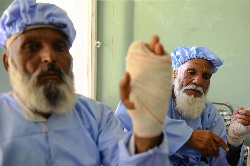 Afghan residents sit in a hospital ward after insurgents cut off their fingers in Herat on June 15, 2014.Afghan police hunted down and killed two Taleban insurgents who cut off the fingers of 11 elderly men who voted in the presidential electio