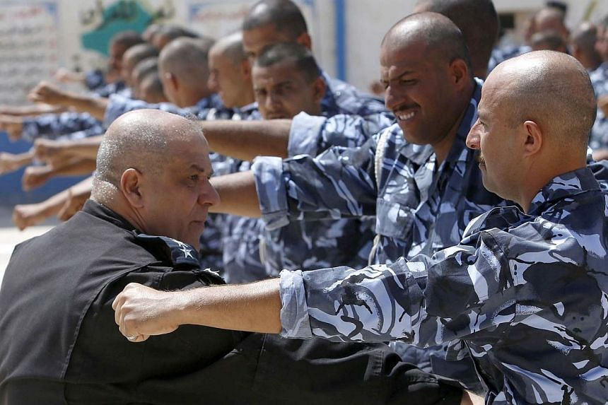 Newly-recruited Iraqi volunteers, wearing police force uniforms, take part in a training session on June 17, 2014, in the central Shi'ite Muslim city of Karbala.-- PHOTO: AFP