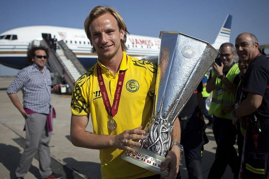 Sevilla's Croatian midfielder Ivan Rakitic poses with the Europa League trophy upon his team's arrival at Sevilla's airport one day after winning the Europa League final over Benfica on May 15, 2014. -- PHOTO: AFP
