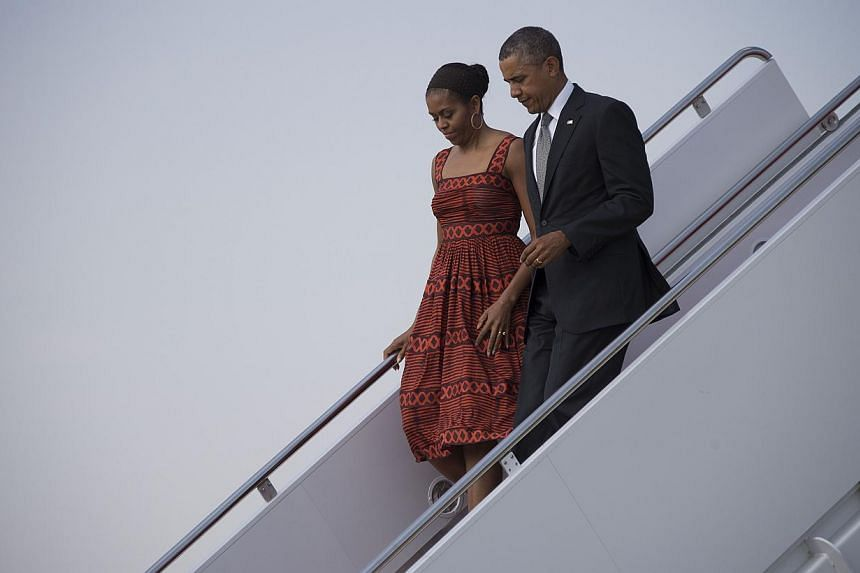 US President Barack Obama (right) and First Lady Michelle Obama walk off Air Force One at Joint Base Andrews, Maryland, on June 16, 2014. -- PHOTO: AFP