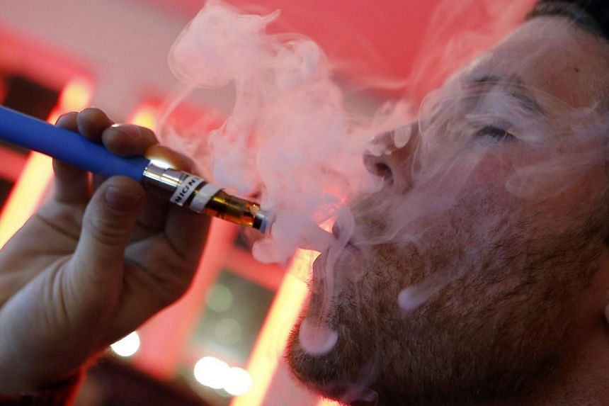 A customer puffs on an e-cigarette at the Henley Vaporium in New York City in this file photo taken on Dec 18, 2013. -- PHOTO: REUTERS