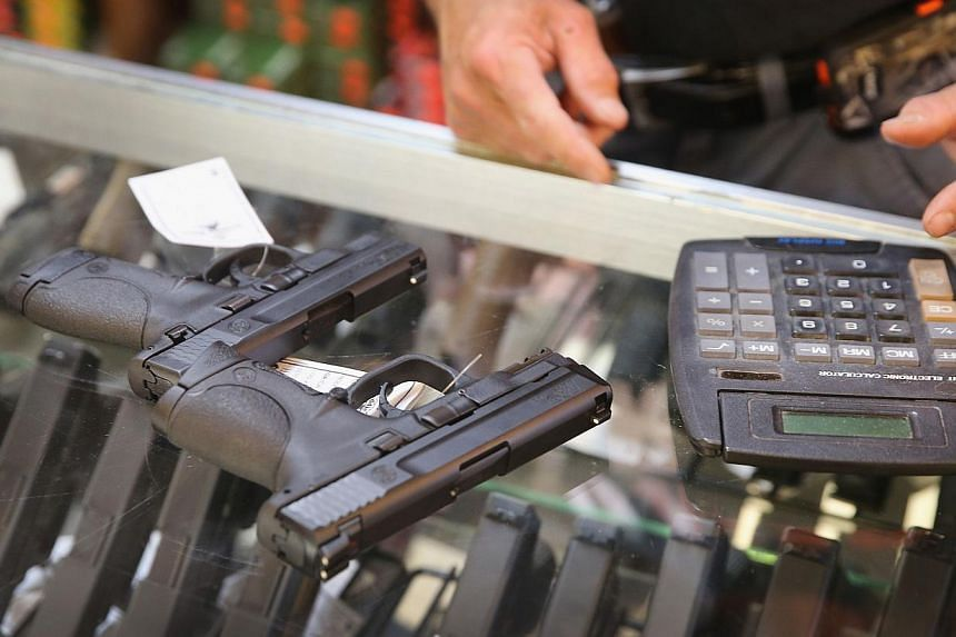 A customer shops for a handgun at Freddie Bear Sports in Tinley Park, Illinois on June 16, 2014. -- PHOTO: AFP