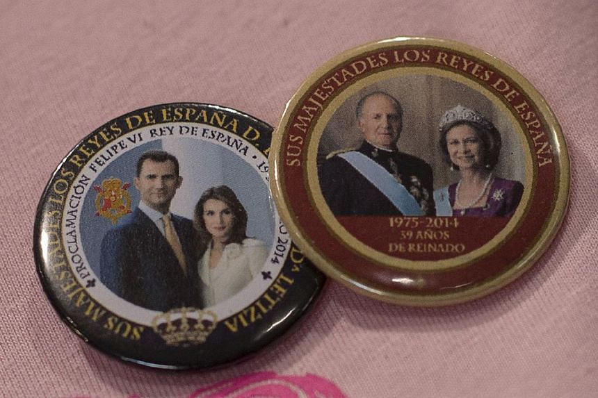 A picture taken on June 14, 2014 shows a badges with portraits of Spain's king-in-waiting, Prince Felipe, and his wife Letizia and Spain's King Juan Carlos and Queen Sofia at a souvenir shop in Madrid. -- PHOTO: AFP