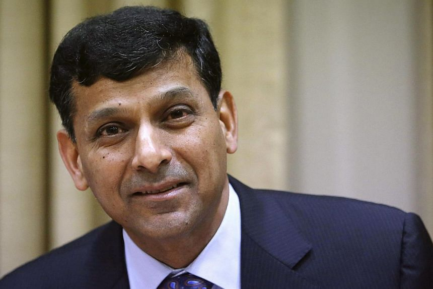Reserve Bank of India (RBI) Governor Raghuram Rajan smiling after arriving for a quarterly interest rate review briefing at the RBI headquarters in Mumbai in this October 29, 2013 file photo. India is ready to deal with any external shock arising fro