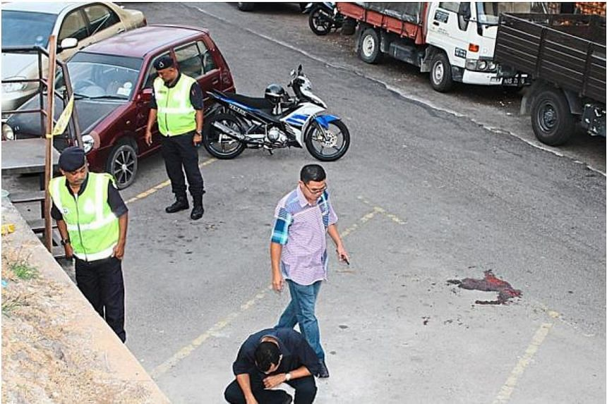 Police officers inspecting the scene of the shooting in Kajang. -- PHOTO: THE STAR/ASIA NEWS NETWORK