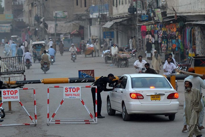 Pakistan Anti-Terrorist Squad (ATS) personnel search a car at a checkpoint in Bannu near the border with the North Waziristan tribal agency on June 16, 2014. Pakistan Prime Minister Nawaz Sharif has urged Afghan President Hamid Karzai to help st