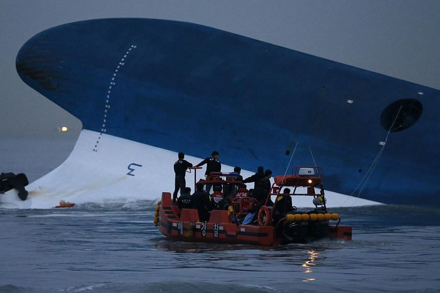 """Maritime police search for missing passengers in front of the South Korean ferry """"Sewol"""" which sank at the sea off Jindo in this April 16, 2014, file photo.The surviving crew of the Sewol argued on Tuesday that once the coast guard reached the"""