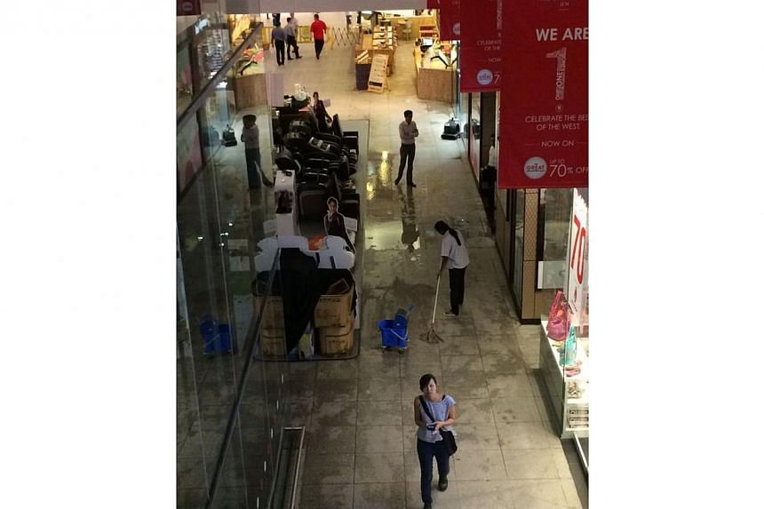 Staff cleaning up after sprinklers went off at JEM shopping mall.-- ST PHOTO: LIM YAOHUI
