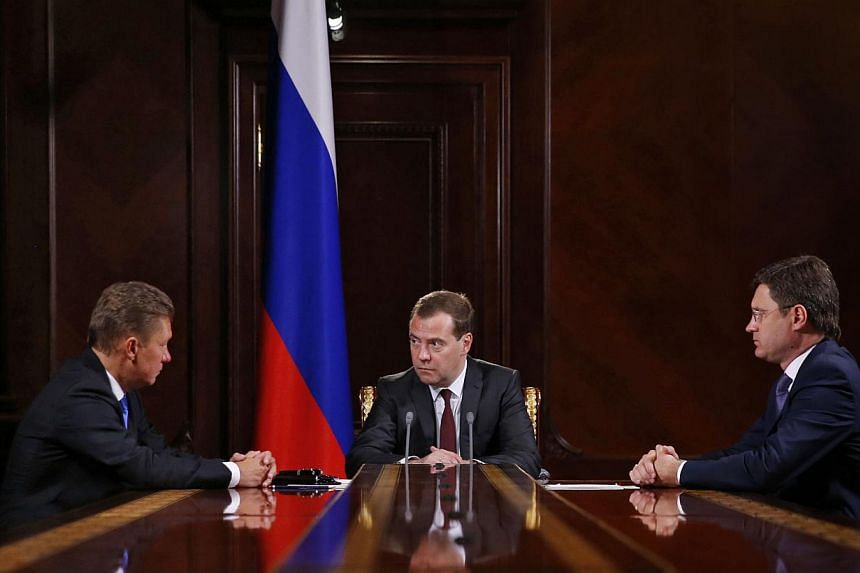 Russia's Prime Minister Dmitry Medvedev (centre) confers with gas giant Gazprom CEO, Alexei Miller (left), and Energy Minister Alexander Novak (right) during their meeting in the Gorki residence outside Moscow on June 16, 2014, following a round of t