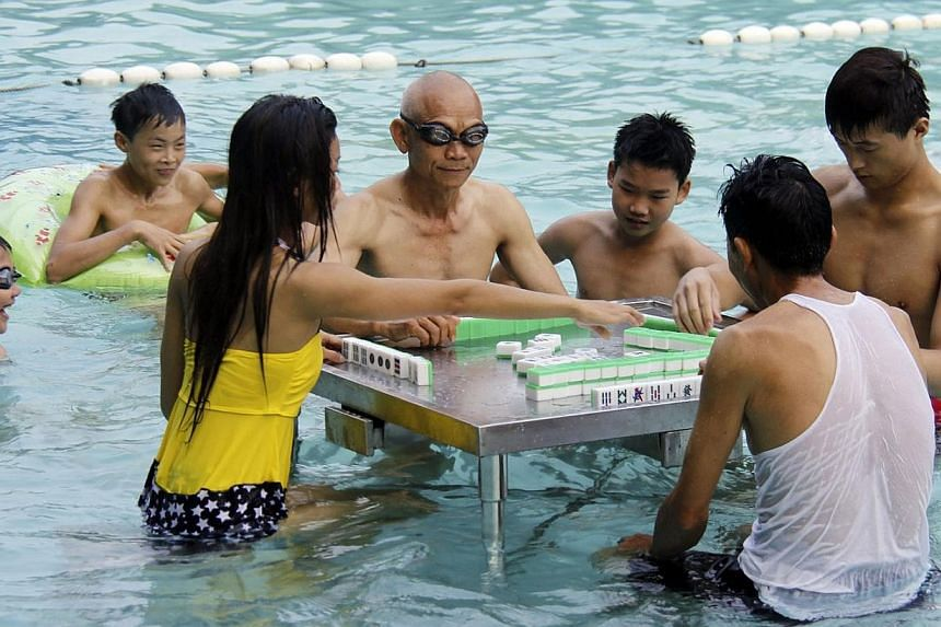 Residents play mahjong in a swimming pool to provide relief from the hot weather in Foshan, Guangdong province on Monday, June 16, 2014. The temperature in Foshan reached 35 deg C on Monday. -- PHOTO: REUTERS