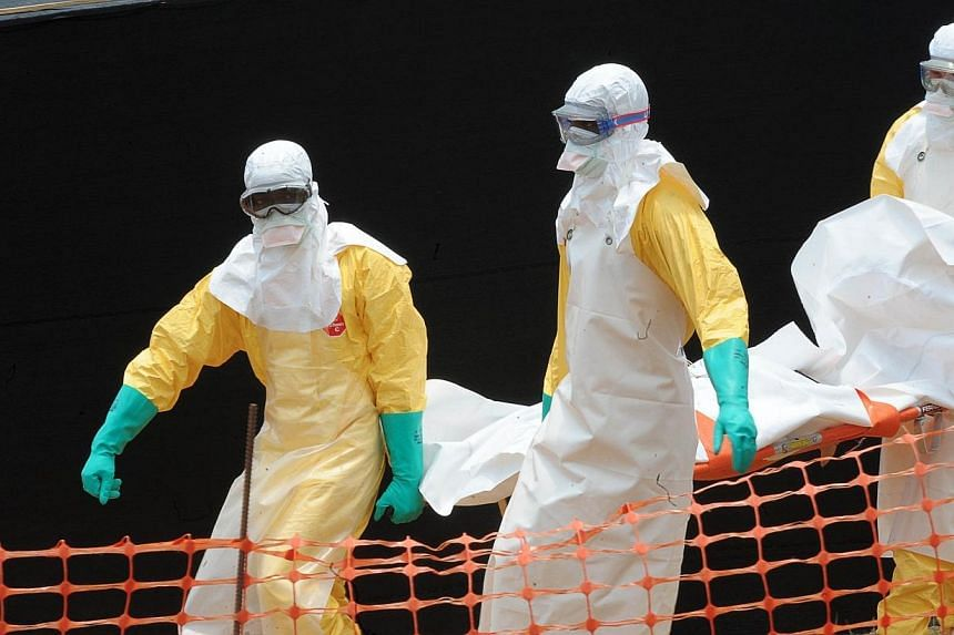"""A file photo taken on April 1, 2014 shows staff of the """"Doctors without Borders"""" ('Medecin sans frontieres) medical aid organisation carrying the body of a person killed by viral haemorrhagic fever, at a center for victims of the Ebola virus in Gueke"""