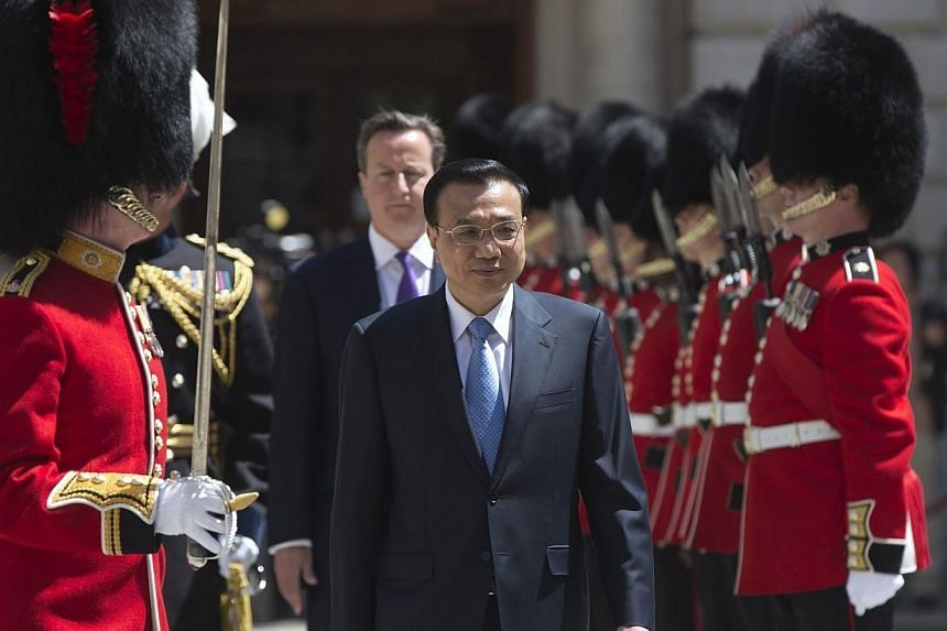 Chinese Premier Li Keqiang is followed by Britain's Prime Minister David Cameron as he inspects a Guard of Honour at the Treasury building in London on June 17, 2014. Mr Li said on Wednesday, June 18, 2014, that China's economy would not su
