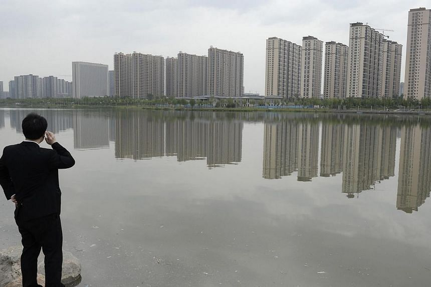 A man talks on his phone near a new residential compound in Taiyuan, Shanxi province on May 11, 2014.Optimism among Asia's top companies has hit its highest level in two years, amid positive political changes in the region and upbeat signs from