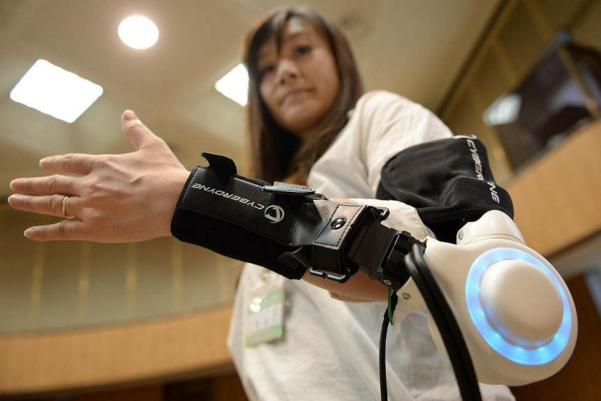 An official of Kawasaki City demonstrates a new powered exoskeleton to assist movement of an arm developed by Japan's robot suit venture Cyberdyne during a press conference in Kawasaki, suburb of Tokyo, on June 18, 2014. A Japanese robot-maker o