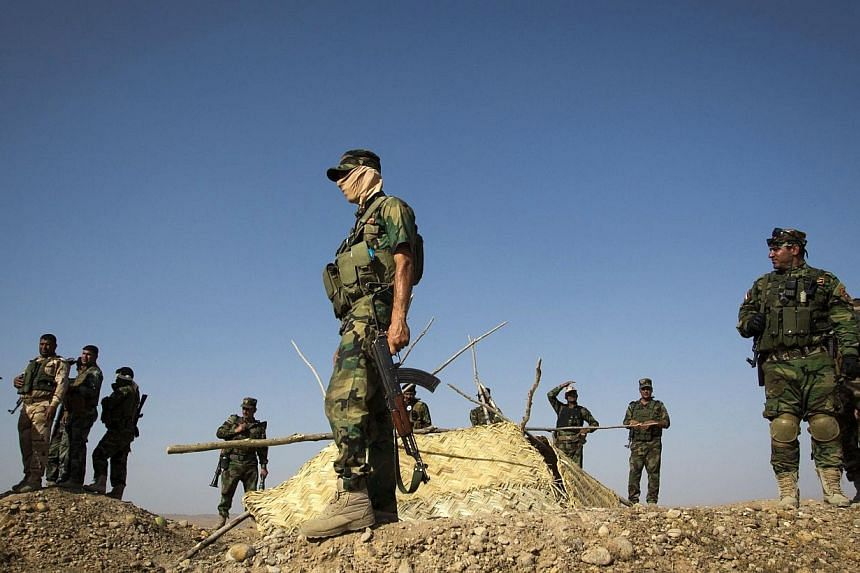 Members of Kurdish Peshmerga forces stand atop a hill during clashes with militants of the Islamic State of Iraq and the Levant (ISIL) jihadist group in Jalawla in the Diyala province on June 14, 2014. The United States is concerned with the situatio