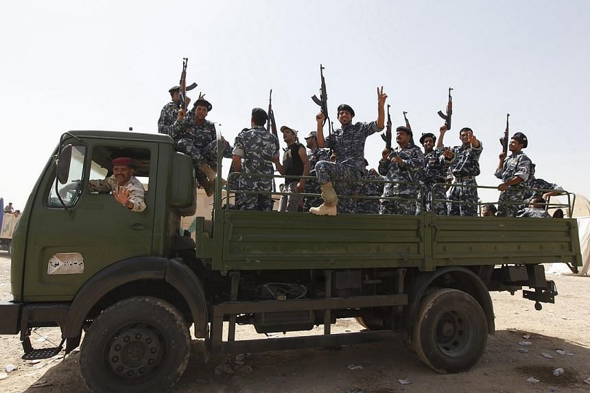 Shi'ite volunteers, who have joined the Iraqi army to fight against the predominantly Sunni militants from the radical Islamic State of Iraq and the Levant (ISIL) who have taken over Mosul and other northern provinces, gesture with their weapons from