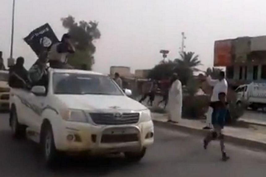 An image grab taken from a video uploaded on Youtube on June 17, 2014, allegedly shows militants from the Islamic State of Iraq and the Levant (ISIL) parading with their group's flag in the northern city of Baiji in the in Salaheddin province. P