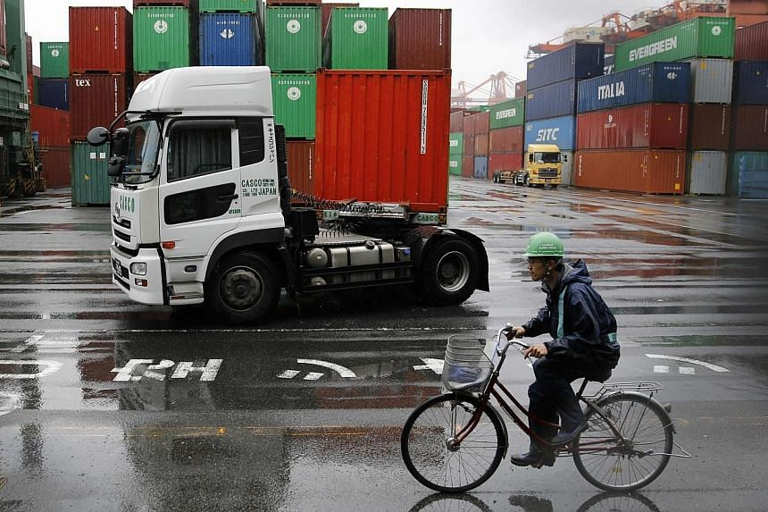 A worker rides a bicycle in a container area at a port in Tokyo May 21, 2014. Japan's exports suffered their first annual decline that month. -- PHOTO: REUTERS