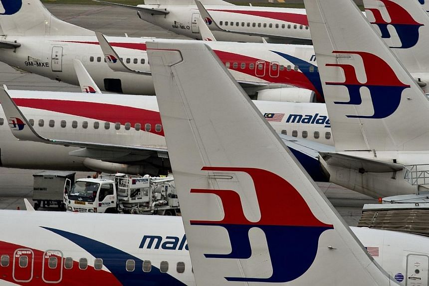 Airport groundstaff walk past Malaysia Airlines planes parked on the tarmac at the Kuala Lumpur International Airport in Sepang on June 17, 2014.Malaysia Airlines (MAS) has been told by Malaysia's Transport Ministry to give Muslim stewardesses